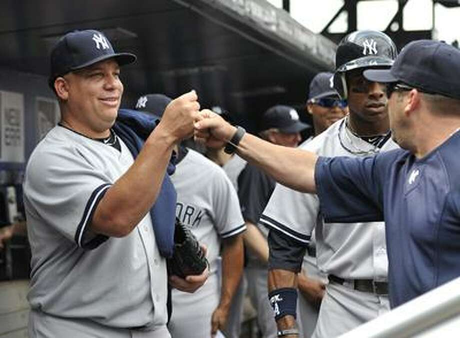 New York Yankees starting pitcher Bartolo Colon bumps fist with teammates in the dugout before a baseball game against the New York Mets on Saturday, July 2, 2011, at Citi Field in New York. Colon pitched six shutout innings in the Yankees 5-2 win. (AP Photo/Kathy Kmonicek) Photo: AP / FR170189 AP