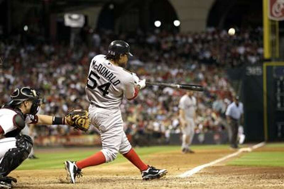 Boston Red Sox's Darnell McDonald (54) hits a three-run home run as Houston Astros catcher J.R. Towles reaches for the pitch during the eighth inning of an interleague baseball game, Saturday, July 2, 2011, in Houston. (AP Photo/David J. Phillip) Photo: AP / AP