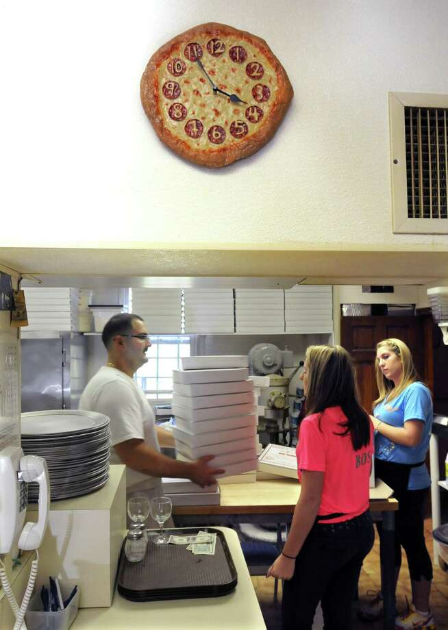 Frank Carofano of Woodbridge (left), and Monica Croce (center) and her twin sister Mallory, both of Wallingford, get boxes ready for the evening rush at Ernie's Pizzeria. The Croces are nieces of owner Pat DeRiso. (Photo by Mara Lavitt/New Haven Register)
