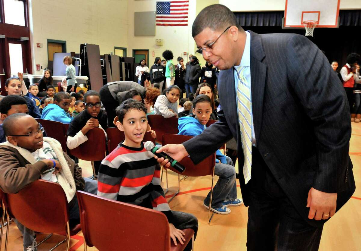 NEW HAVEN--NEW HAVEN-Tyler Reid (C), a fifth grade student at Edgewood School, answers a question posed by Hillhouse principal, Kermit Carolina (R). Carolina, and Hillhouse scholar-athletes visited the younger students for a Connecticut Mastery Test pep rally held at Edgewood. At Left is John Chappelle Melanie Stengel/Register3/1/11