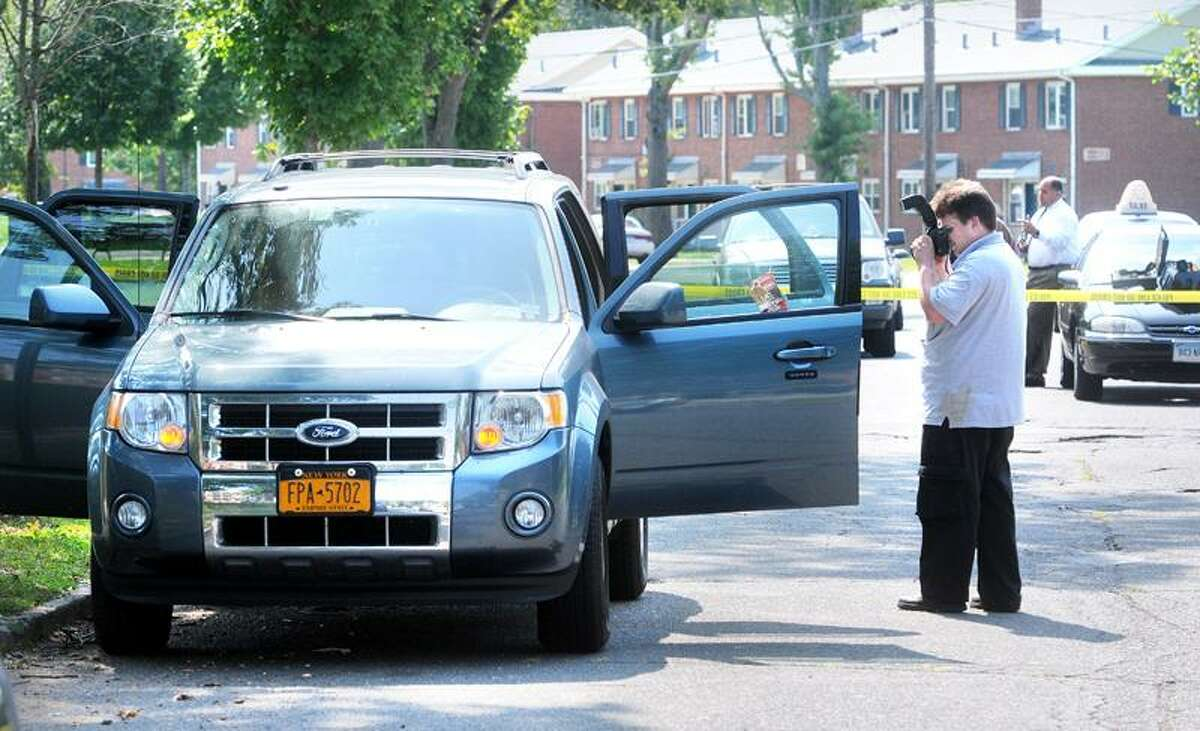 New Haven Detective Matthew Prinz photographs a Ford Escape on South Genesee Street in New Haven, where the body of Timothy