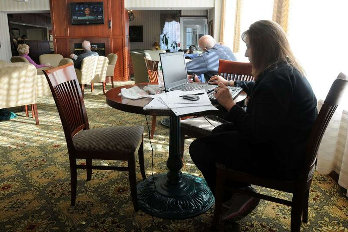 The Clarion Hotel and Suites in Hamden has become home to many displaced from the storm, in addition to the usual mix of visitors. Victoria Rutigliano of Middlefield usually works out of her home; here, she sets up her office on a table in the hotel lobby. Mara Lavitt/Register