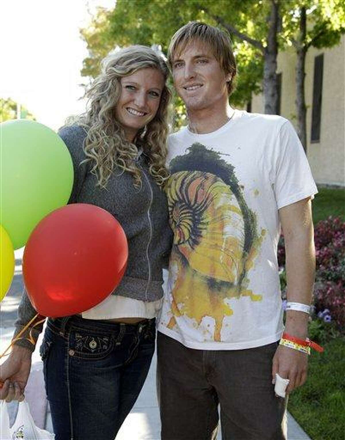 Eric Tarantino leaves a San Jose, Calif., hospital with his girlfriend Krista Herr, Monday, Oct. 31, 2011, after he was attacked by a shark at Marina State Beach on Saturday. Tarantino, 27, was bitten on the neck, arm and hands. (AP Photo/Paul Sakuma)