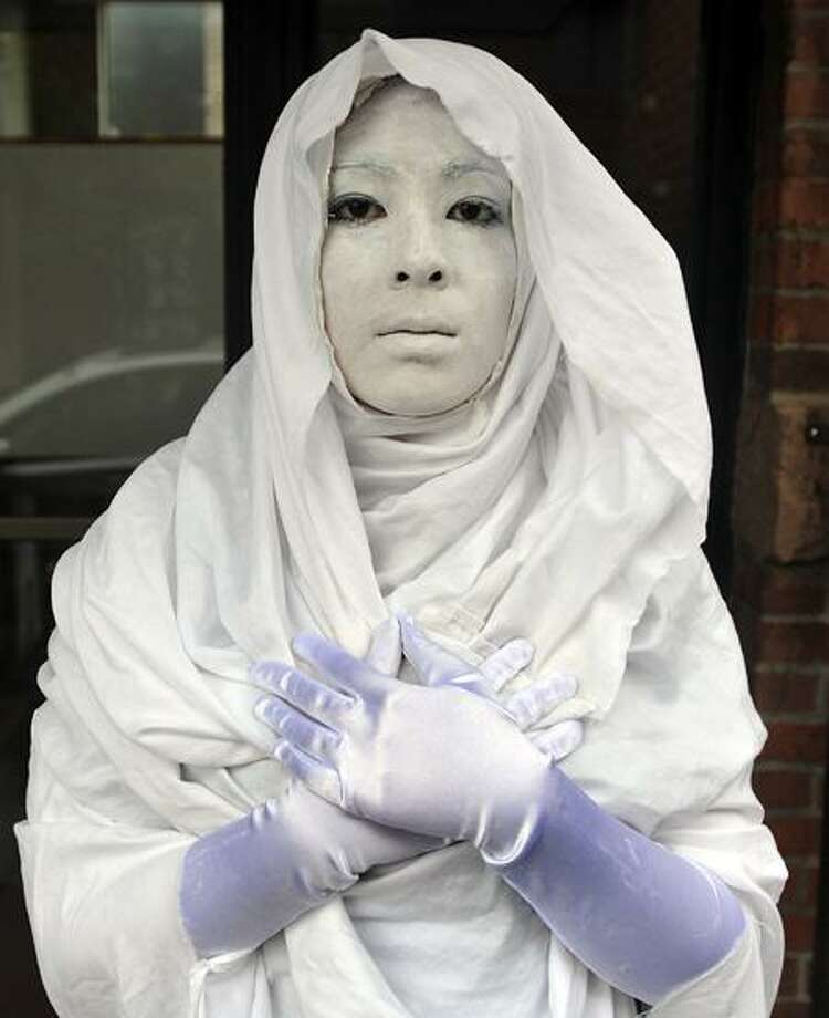 """Hopkins senior Laura Paik stands on Church Street in silence as part of her art project, """"The Art of the Living Statue."""" Peter Casolino/Register"""