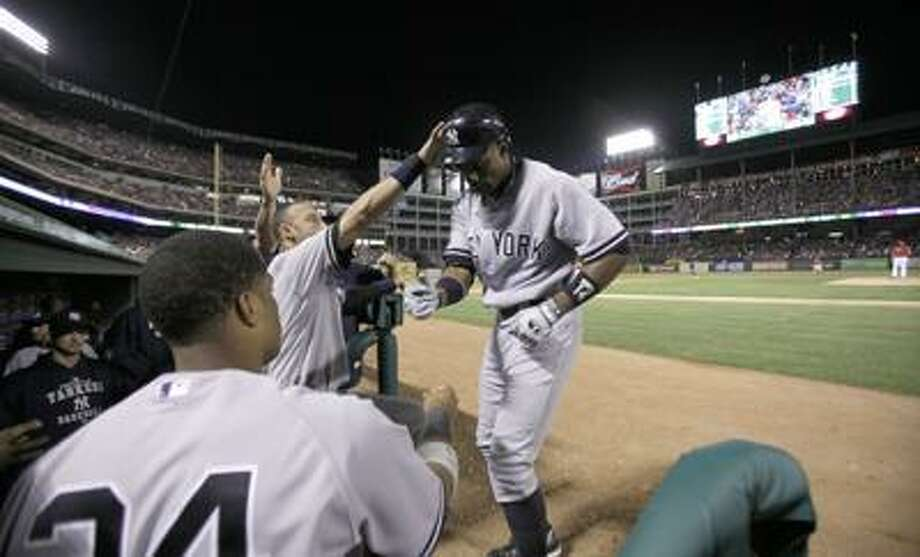 New York Yankees Curtis Granderson, right, gets congratulations from Derek Jeter, center, and Robinson Cano (24) as Granderson heads into the dugout after hitting a solo home run in the seventh inning of a baseball game against the Texas Rangers in Arlington, Texas, Friday, May 6, 2011.  (AP Photo/LM Otero) Photo: AP / AP