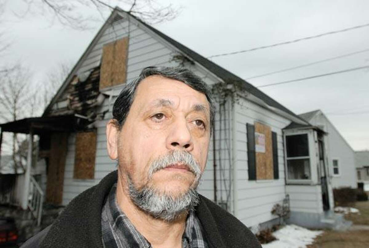 Ivan Cordero of Hamden, 59, rescued a woman from her burning home after he saw black smoke billowing from the 398 Pine Orchard Road single family residence in Hamden 1/6/11. In the photo Cordero is standing on a sidewalk by the house. Photo by Peter Hvizdak / New Haven Register January 7, 2011 ph2233 #1736 Connecticut