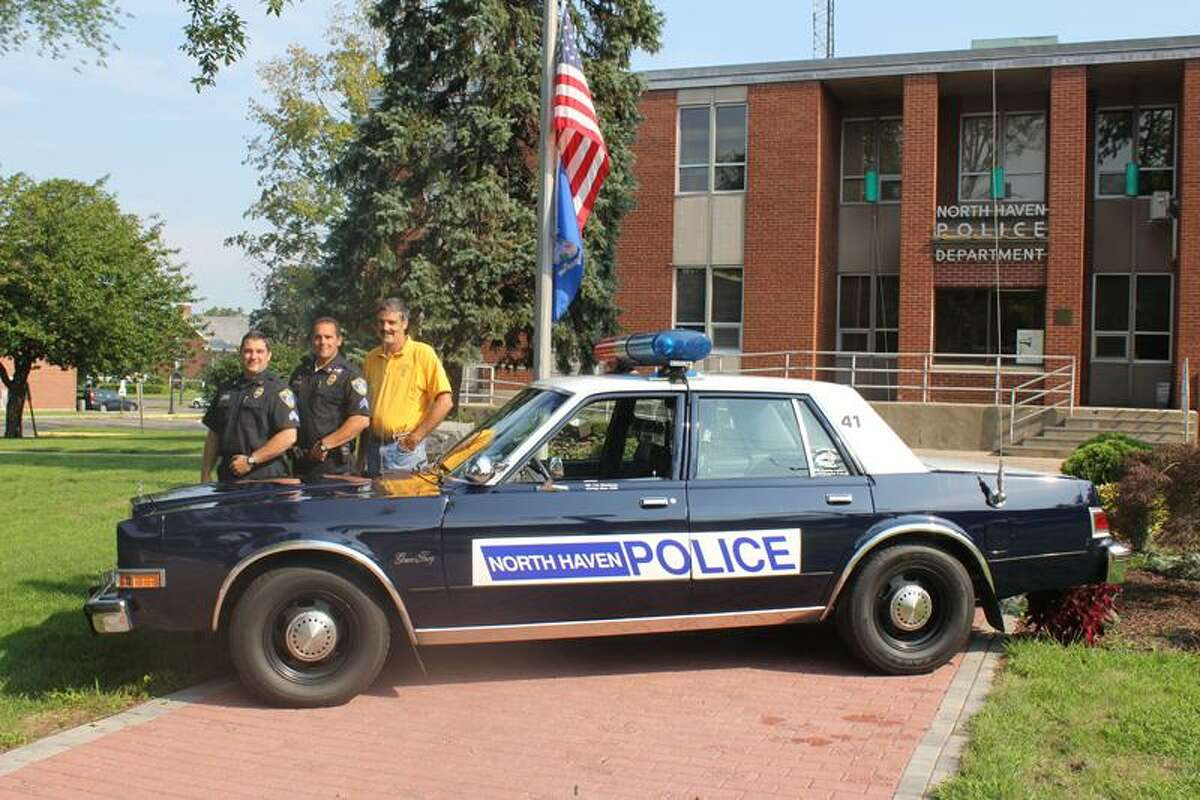 North Haven police Officer Ted Stockmon, Police Benevolent Association President Sgt. Robert DePalma and Sgt. Christopher Thorpe, PBA vice presdient and event organizer, stand next to Stockmon's restored 1989 Plymouth Grand Fury. Contributed photo