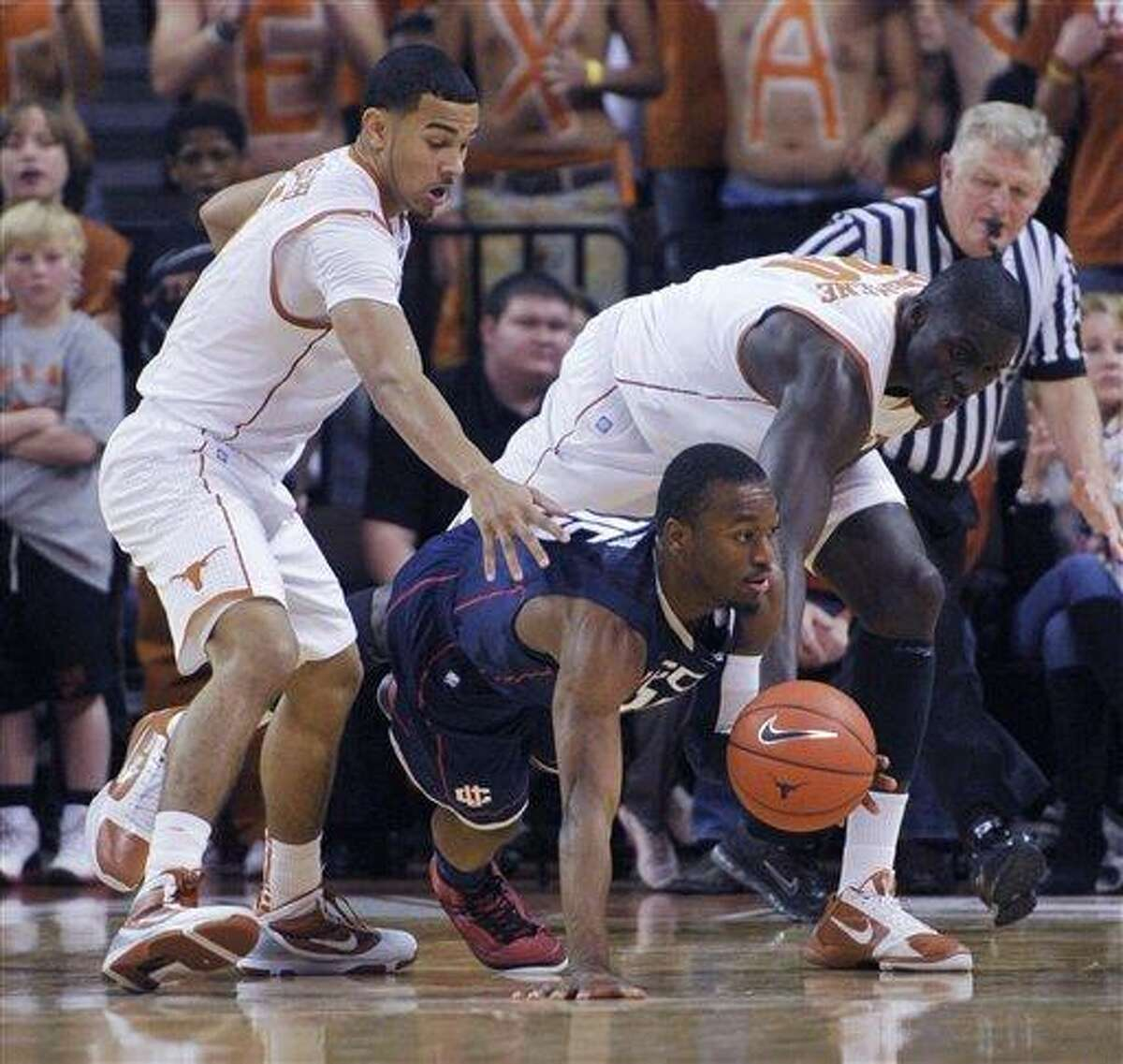 Connecticut guard Kemba Walker, center, goes for the loose ball against Texas guard Cory Joseph, left, and Texas center Alexis Wangmene, right, during the first half in an NCAA college basketball game Saturday, Jan. 8, 2011, in Austin, Texas. (AP Photo/Michael Thomas)