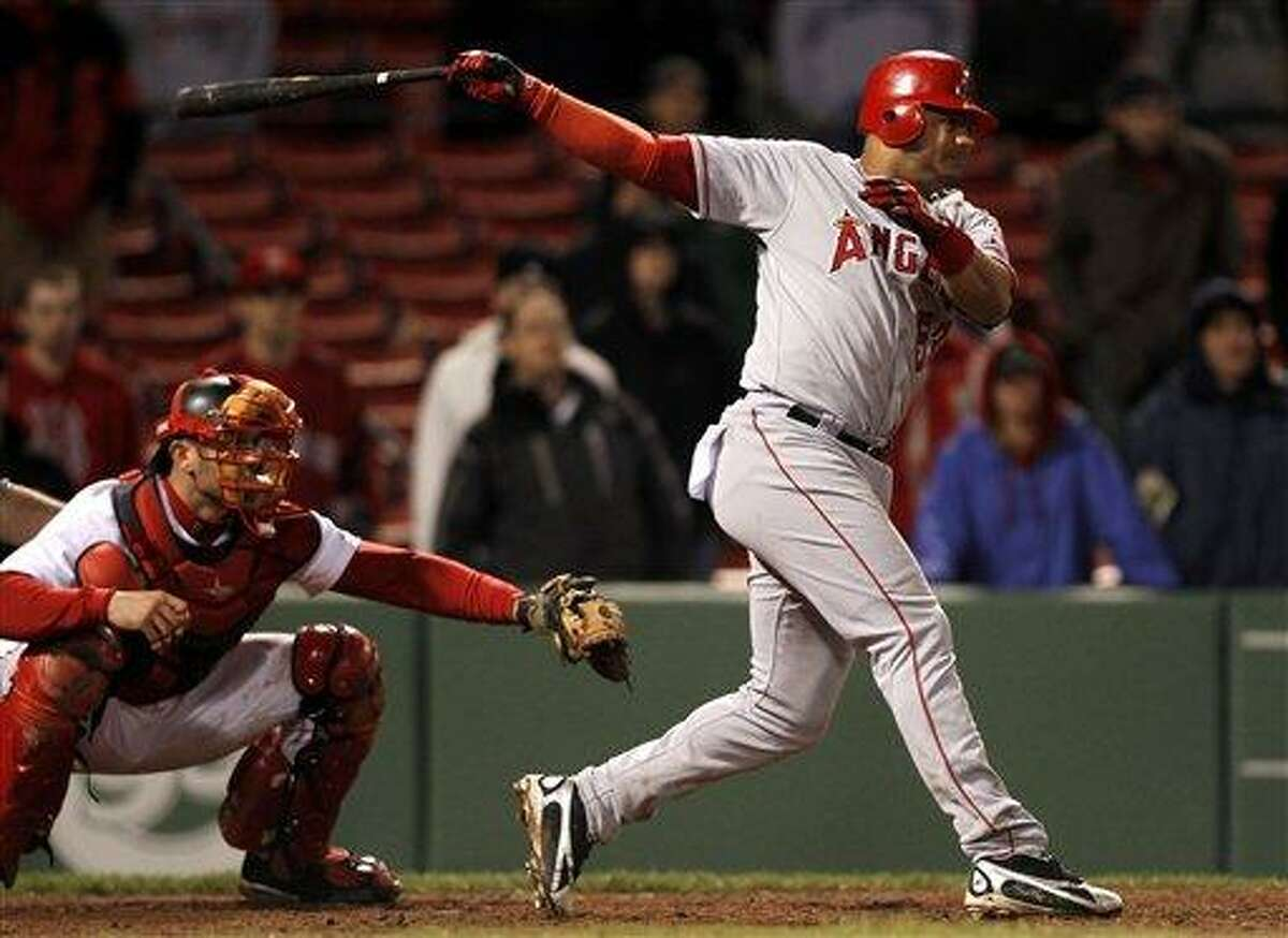 Los Angeles Angels' Bobby Abreu, right, hits a two-run single off a pitch by Boston Red Sox's Daisuke Matsuzaka as Red Sox catcher Jason Varitek looks on left, during the thirteenth inning of a baseball game at Fenway Park in Boston Wednesday, May 4, 2011. The Angels won 5-3. (AP Photo/Steven Senne)