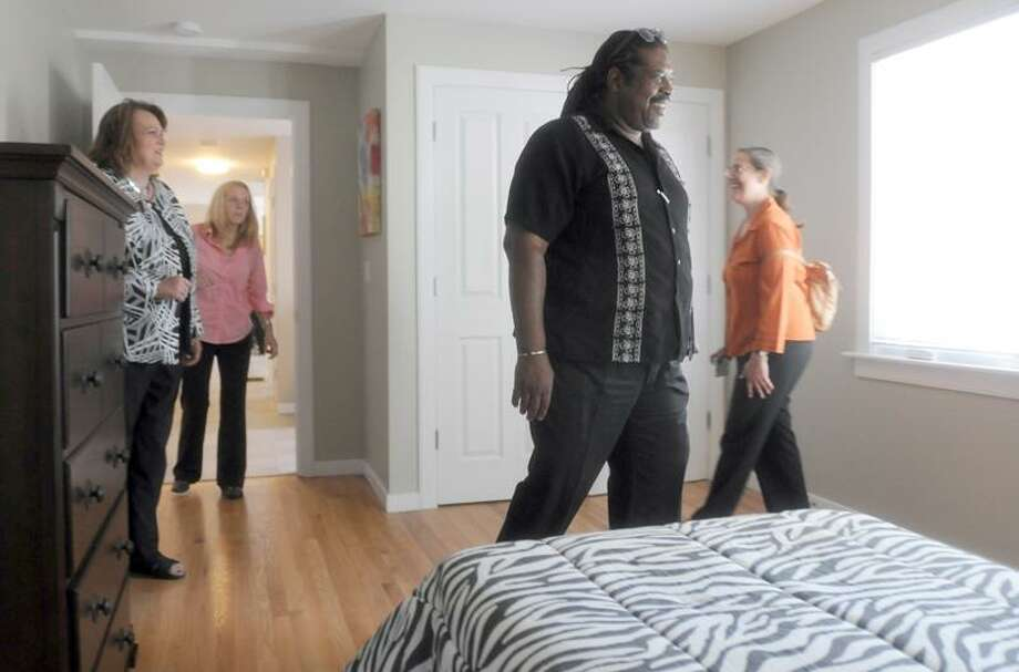 Patti Walker, far left, president and CEO of Continuum of Care, shows off a model apartment Wednesday in the newly developed supportive housing units at 24 Sheldon Terrace in New Haven. Peter Hvizdak /Register photos