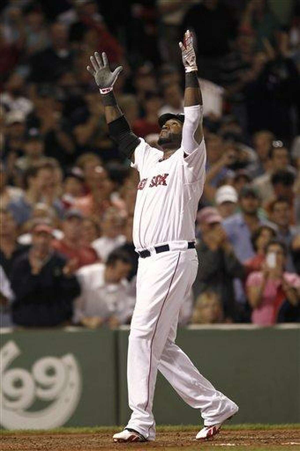 Boston Red Sox designated hitter David Ortiz raises his arms after scoring on his two-run home run against the New York Yankees during the fifth inning Wednesday. The Red Sox beat the Yankees 9-5. (AP Photo)
