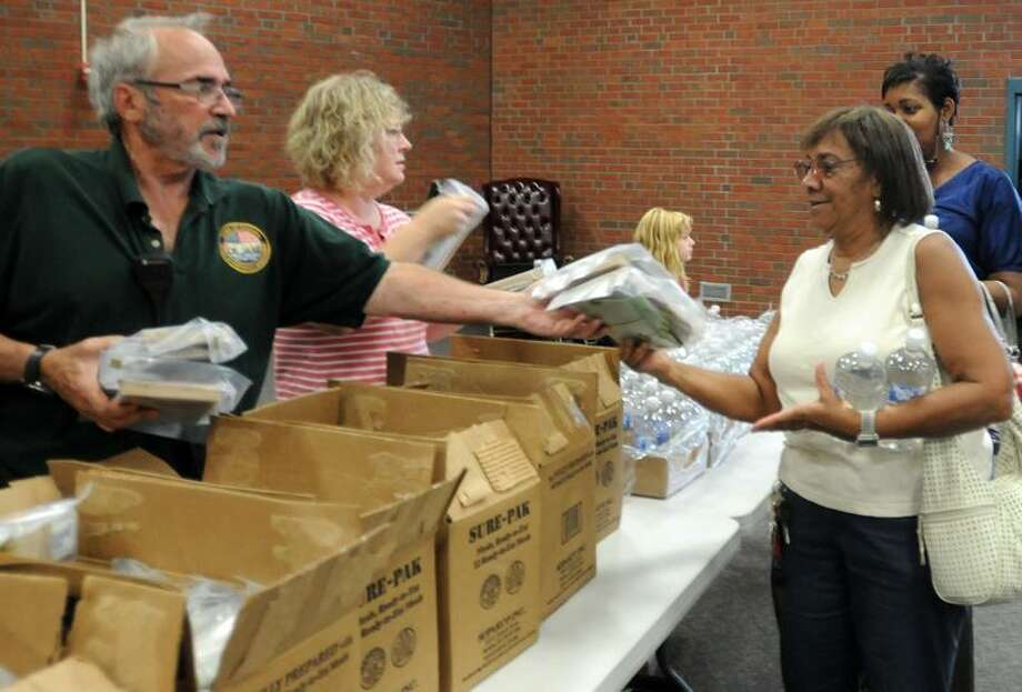 Mark Heinisch of North Haven, left, a Community Emergency Response Team volunteer, and volunteer Pauline Gilbert, center, distribute FEMA supplied water and Meals Ready to Eat at the Hamden's Thornton Wilder Hall Thursday to Gloria Reid of Hamden, 77, and other residents affected by Hurricane Irene. Many Hamden residents have lost their perishable food and are without water.  Photo by Peter Hvizdak / New Haven Register    September 1, 2011       ph2354           Connecticut