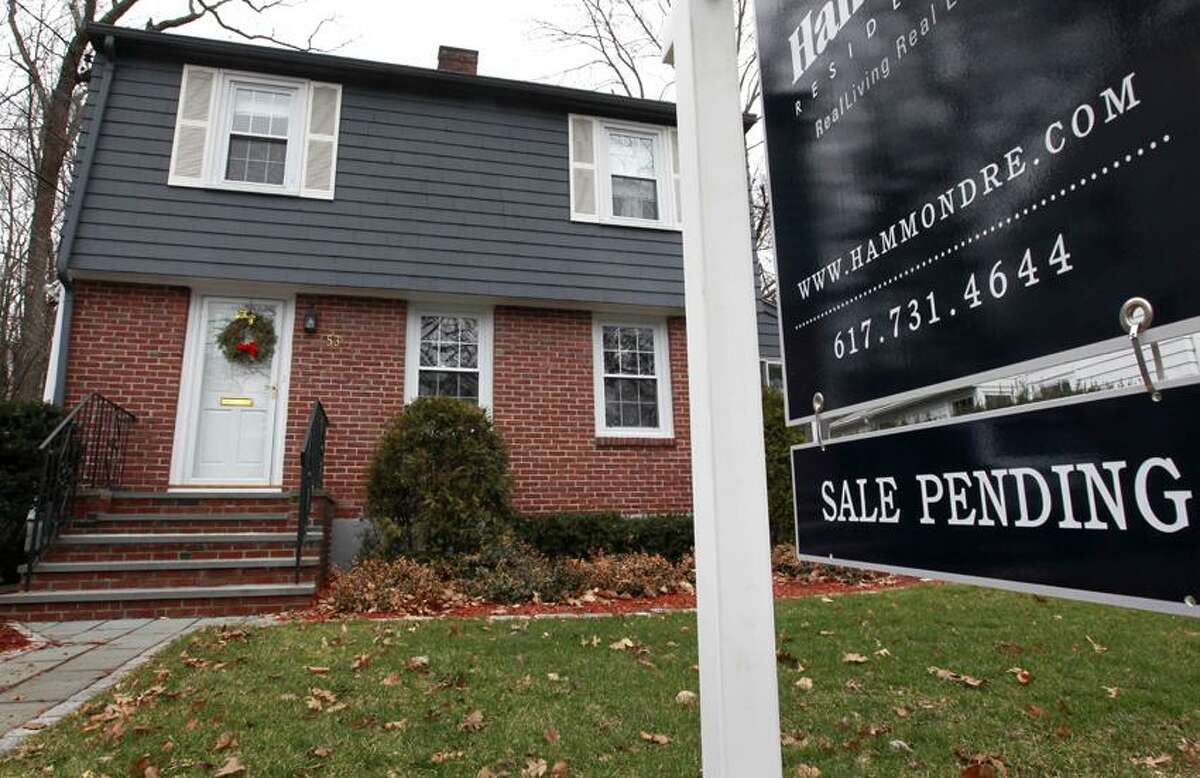 """A """"sale pending"""" sign hangs in front of a single-family home in Brookline, Mass. The number of Americans who signed contracts to buy homes in November rose to the highest level in 1½ years. (Associated Press)"""