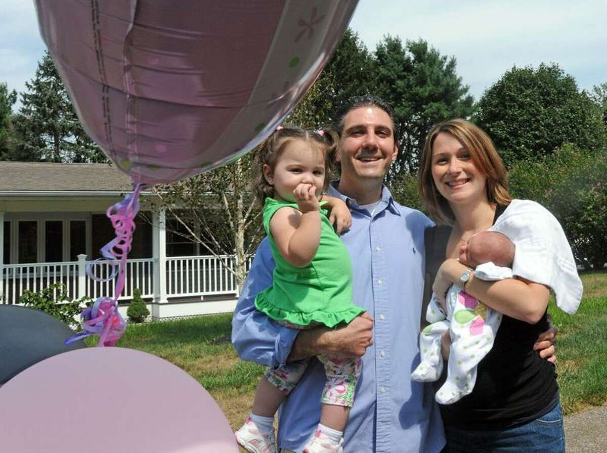 Flanked by ballons in front of his North Haven home, Ron Prisco, holds daughter Olivia 1, while and his wife, Susanne, holds new baby Giuliana. Prisco Giuliana in a car during Hurricane Irene. Peter Hvizdak/Register September 1, 2011 ph2354 Connecticut