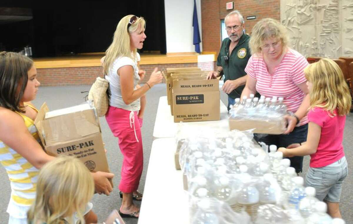 Mark Heinisch of North Haven, top right, a Community Emergency Response Team volunteer, and volunteer Pauline Gilbert with her daughter Samantha, 9, far right, distribute FEMA-supplied water and ready-to-eat meals at the Hamden Library Thornton Wilder Auditorium Friday. Peter Hvizdak/Register