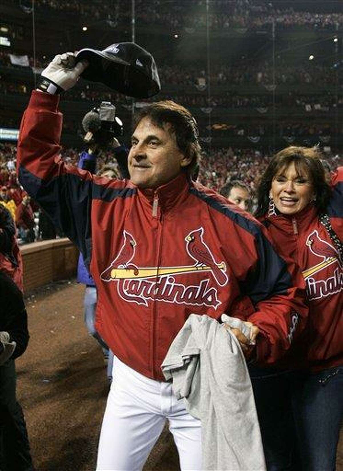 FILE - In this Oct. 27, 2006 file photo, St. Louis Cardinals manager Tony La Russa waves to fans with his wife, Elaine, after the Cardinals won the World Series with a 4-2, Game 5 win over the Detroit Tigers, in St. Louis. La Russa retired as manager of the St. Louis Cardinals on Monday, Oct. 31, 2011, three days after winning a dramatic, seven-game World Series against the Texas Rangers. (AP Photo/Morry Gash, File)