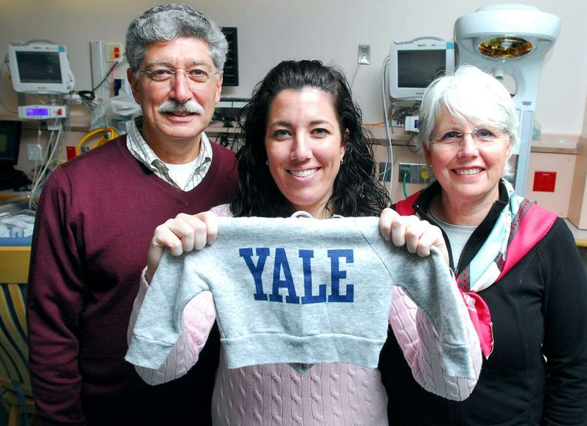 Lauren Ferreira, center, is photographed with her parents Abel, left, and Kathleen of Hyde Park, N.Y., at a Newborn Special Care Room at Yale-New Haven Children's Hospital recently. Lauren was born premature and spent time at the hospital, where starting Friday she works in the same unit. She is holding a sweatshirt from her time spent at the hospital as a baby. (Arnold Gold/Register)