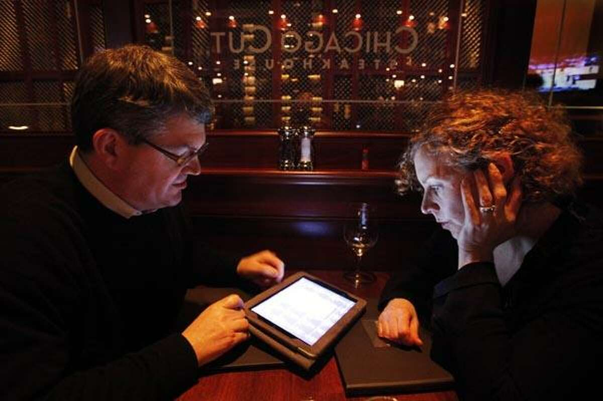 In this photo taken Wednesday, Dec. 1, 2010, Keith, left, and Peg Bragg of Chicago view the wine list on an iPad at Chicago Cut steakhouse in Chicago. The restaurant is just one eatery of several across the U.S. that have started uploading menus and wine lists to the digital devices. (AP Photo/Charles Rex Arbogast)
