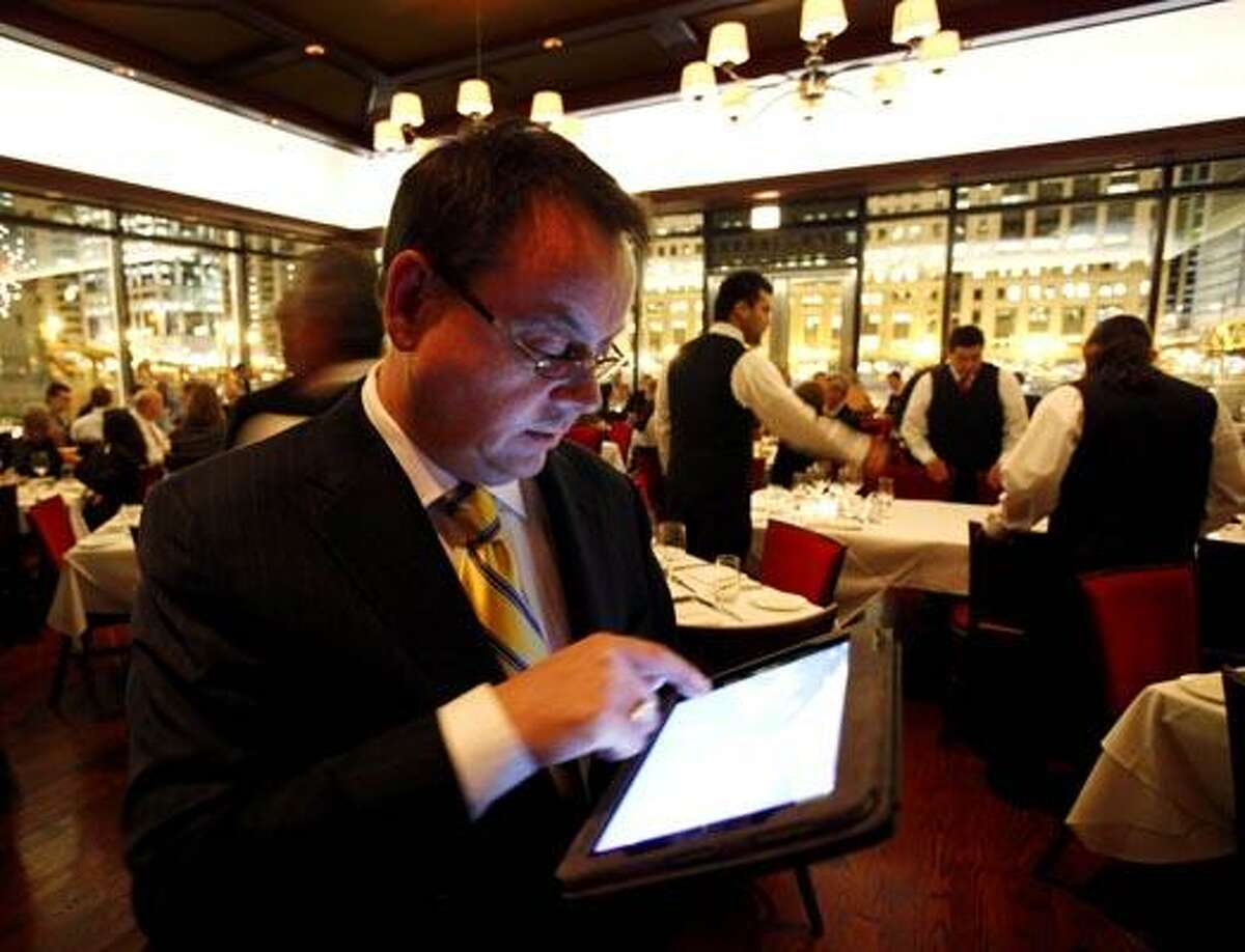 In this photo taken Wednesday, Dec. 1, 2010, Chicago Cut steakhouse managing partner Matt Moore browses the restaurant's wine list on an iPad in Chicago. The restaurant is just one eatery of several across the U.S. that have started uploading menus and wine lists to the digital devices. (AP Photo/Charles Rex Arbogast)