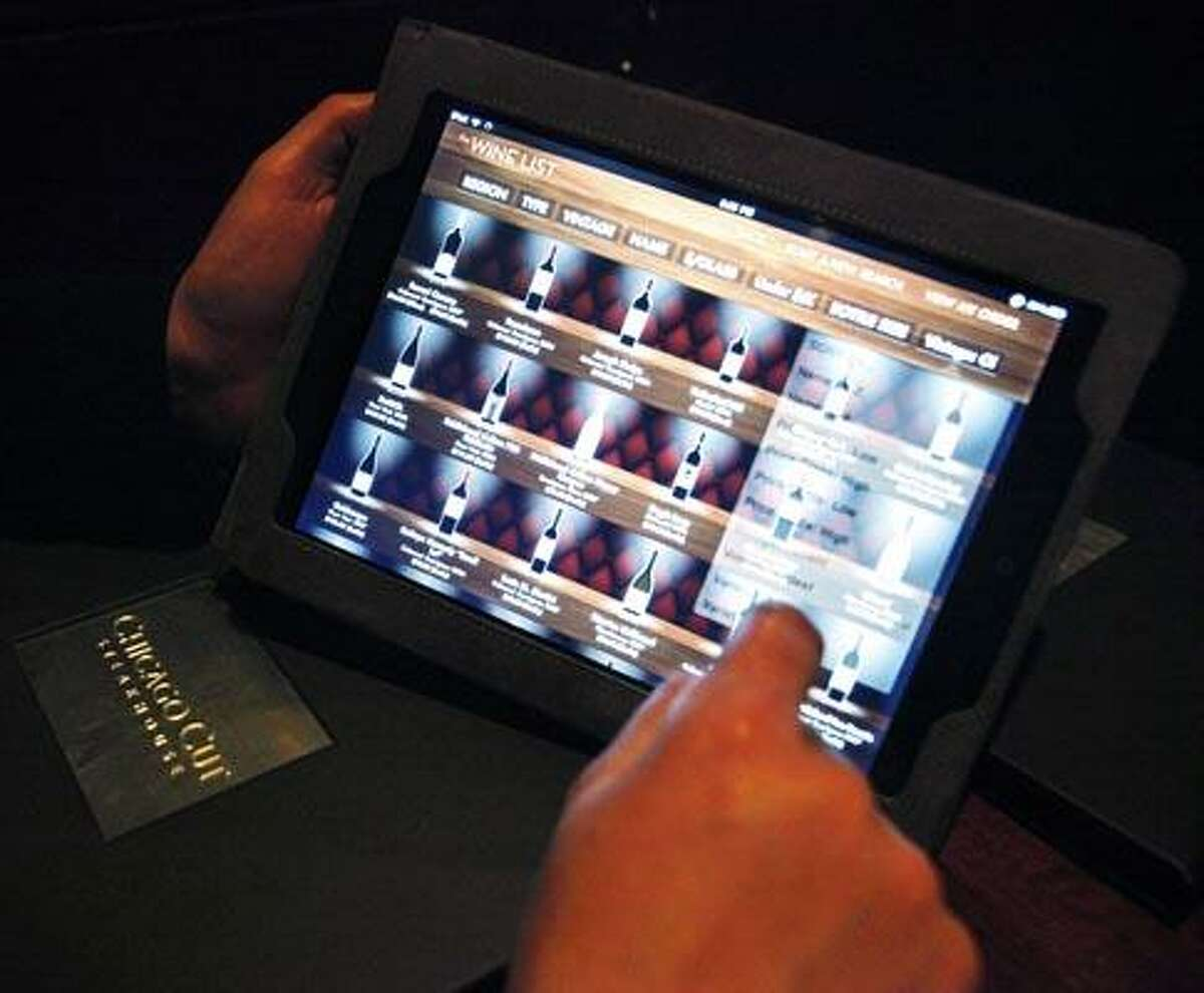 In this photo taken Wednesday, Dec. 1, 2010, Keith Bragg of Chicago navigates the wine list on an iPad at Chicago Cut steakhouse in Chicago. The restaurant is just one eatery of several across the U.S. that have started uploading menus and wine lists to the digital devices. (AP Photo/Charles Rex Arbogast)