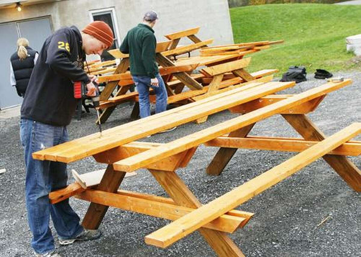 Photo by JOHN HAEGER (Twitter.com/OneidaPhoto) John Beach screws in the top of one of the picnic tables he is building for Holy Cross Academy as part of his Boy Scout Eagle Scout project on Saturday, Oct. 29, 2011 at the Holy Cross Academy in Vernon.