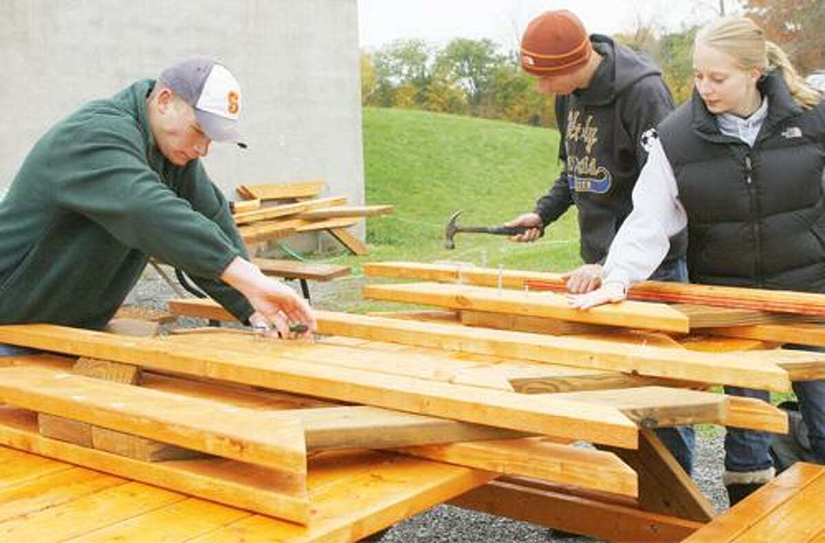 Photo by JOHN HAEGER (Twitter.com/OneidaPhoto) Jon Noble, John Beach, center, and Michaela Dahlem build the legs of the picnic tables that Beach is building for Holy Cross Academy as part of his Boy Scout Eagle Scout project on Saturday, Oct. 29, 2011 at the Holy Cross Academy in Vernon.
