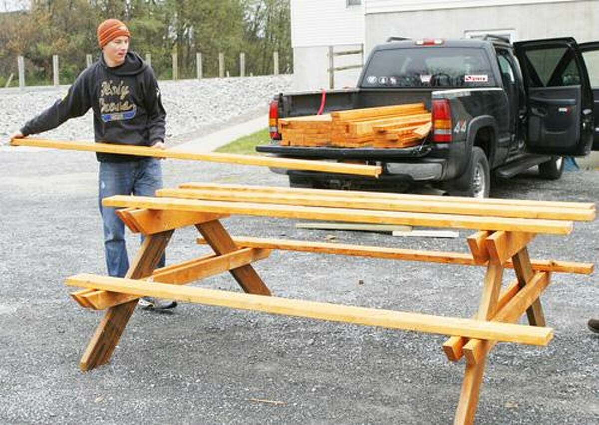 Photo by JOHN HAEGER (Twitter.com/OneidaPhoto) John Beach lays out boards for the top of one of the picnic tables he is building for Holy Cross Academy as part of his Boy Scout Eagle Scout project on Saturday, Oct. 29, 2011 at the Holy Cross Academy in Vernon.