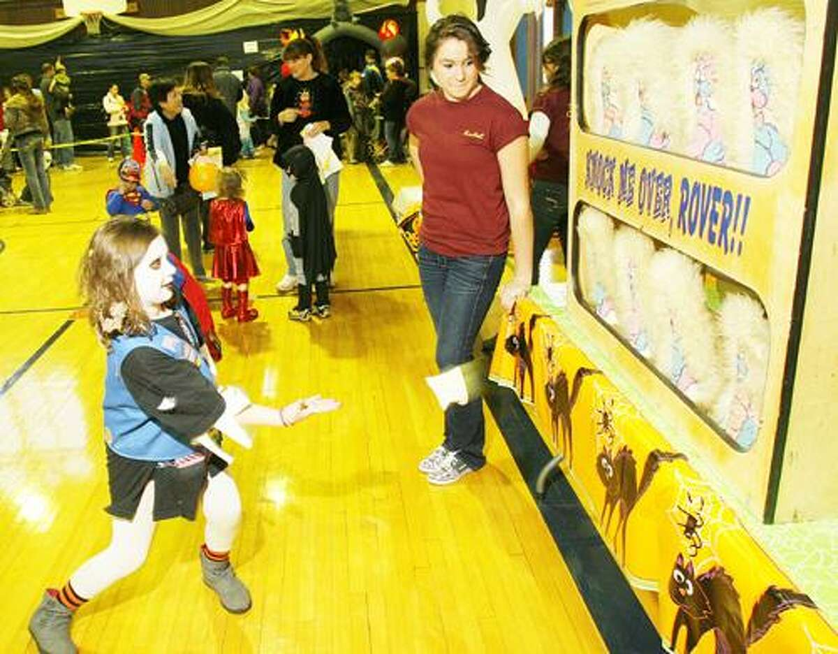 Photo by JOHN HAEGER (Twitter.com/OneidaPhoto) Hannah Loosman, 8, of Oneida, tests her skills as she tries to knock down the cats with a bean bag to win a prize during the city of Oneida Rec Departments annual Halloween Party on Saturday, Oct. 29, 2011 at the armory. Watching is Z Club member Rachel Labrecque.