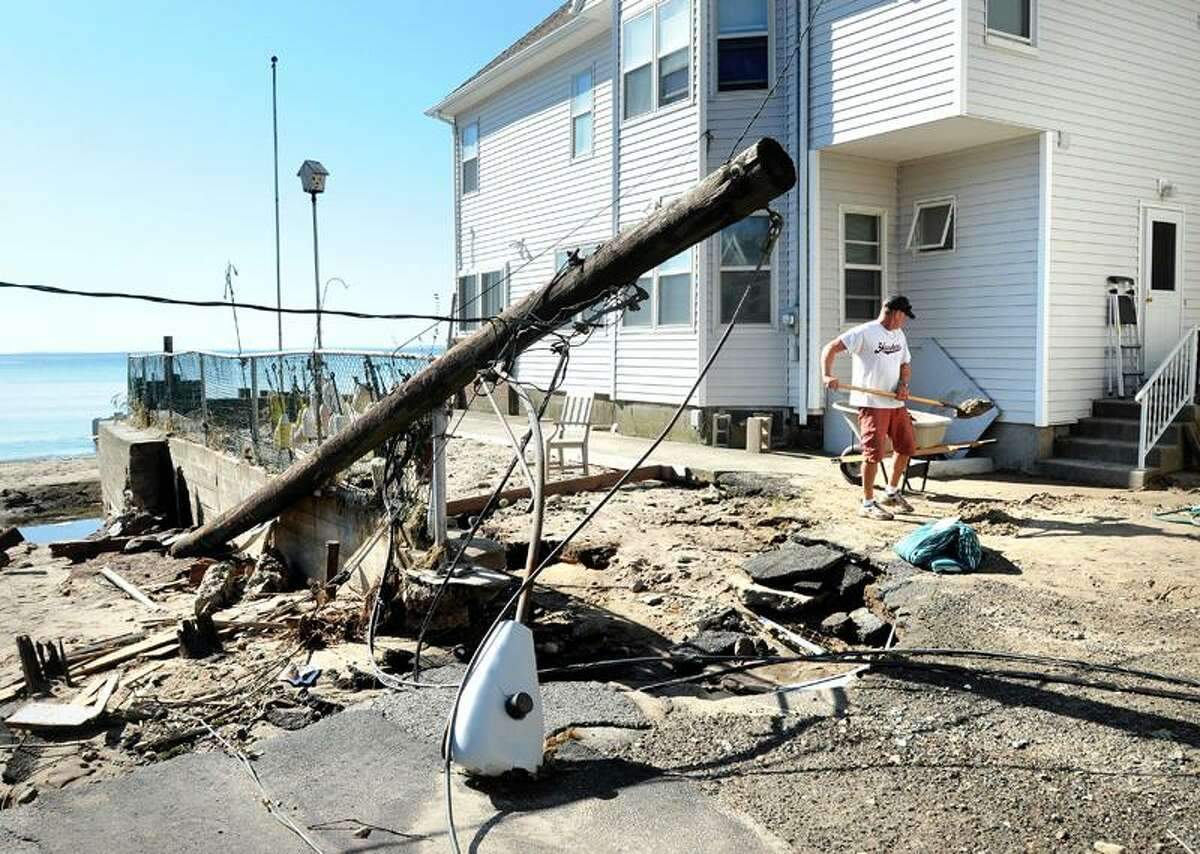 Brian Ragozzine of Southington shovels sand from his parents' shore water home on Wildemere Beach in Milford Monday. A utility pole was a casualty of the storm. (Arnold Gold/Register)