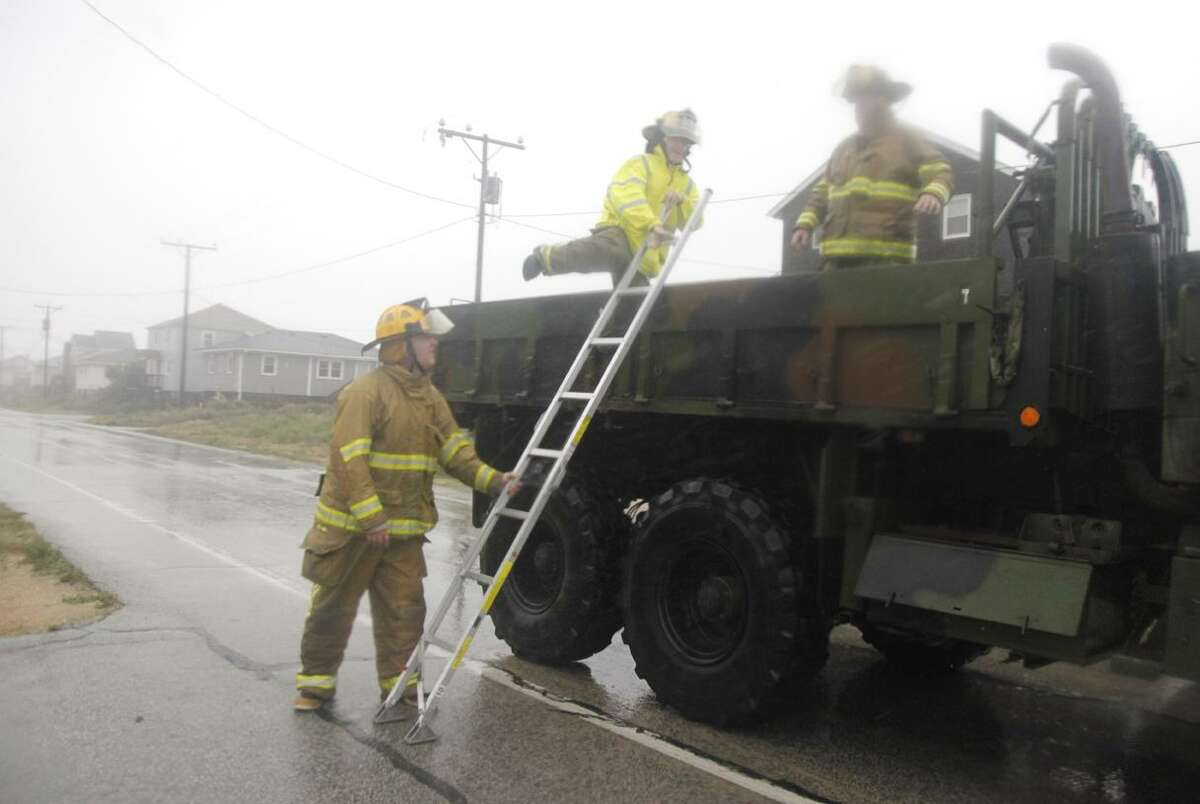 Using a military surplus truck, firefighters go from house to house fastening down gas tanks in Kitty Hawk, N.C., Saturday, Aug. 27, 2011, as Hurricane Irene reaches the North Carolina coast. (AP Photo/Charles Dharapak)