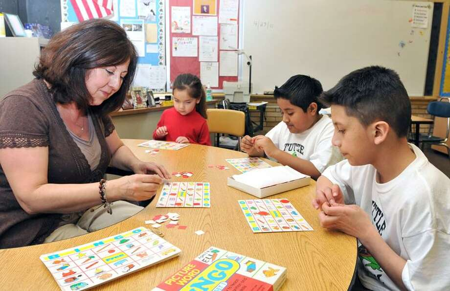 From right, Jeremy Maldonado, 10, Diego Ortiz, 8, and Camilla Tapia, 4, work on a language exercise with Elizabeth Hume, teacher coordinator for the East Haven CARES program at Tuttle School earlier this week.