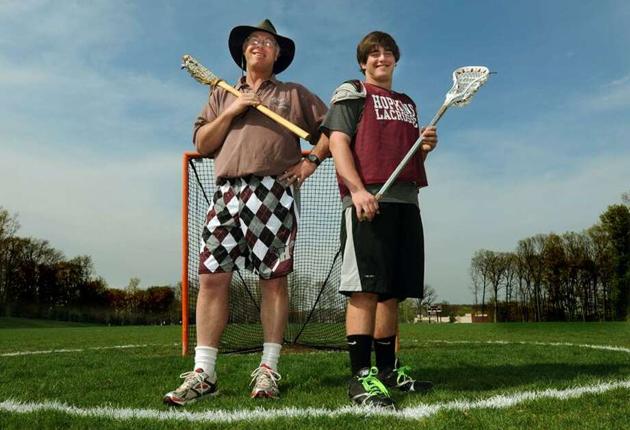 Hopkins lacrosse coach (33 years) Sandy MacMullen left of New Haven and current captain Mark Festa of Orange right on the Hopkins field.  Photo by Mara Lavitt/New Haven Register5/3/11