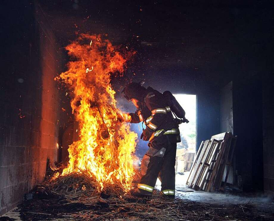 New Haven-- A training officer lights hay and palettes on fire in a room at the New Haven Fire academy burn building for recruits to train. After the fire got going, the room .  Photo by Peter Casolino/New Haven Register05/03/11 Cas110503