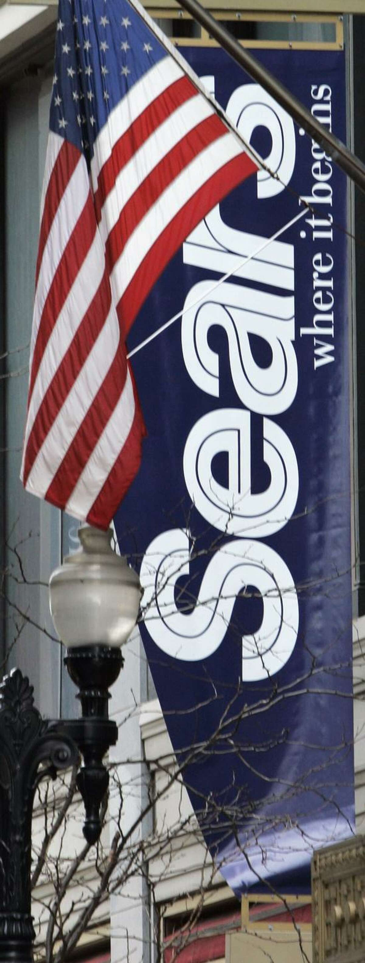 A banner is seen on the exterior of the Sears department store in downtown Chicago. Sears Holdings Corp. said Tuesday it plans to close 100 to 120 of its Sears and Kmart stores as its holiday sales disappointed and it looks to reduce costs.(Associated Press)