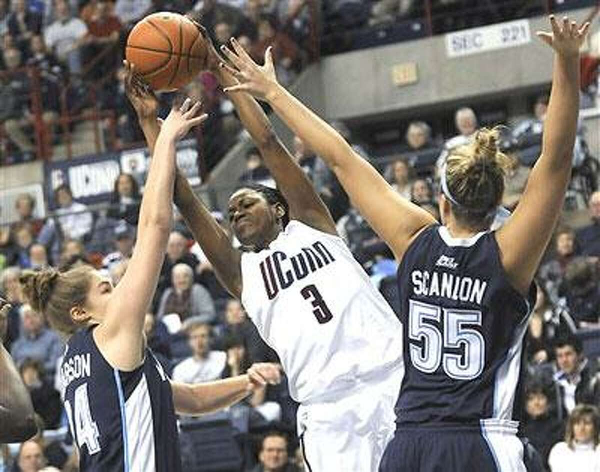 Villanova's Megan Pearson, left, and Heather Scanlon, right, try to stop Connecticut's Tiffany Hayes as Hayes grabs a rebound in the first half of an NCAA college basketball game in Storrs, Conn., Wednesday, Jan. 5, 2011. (AP Photo/Bob Child)