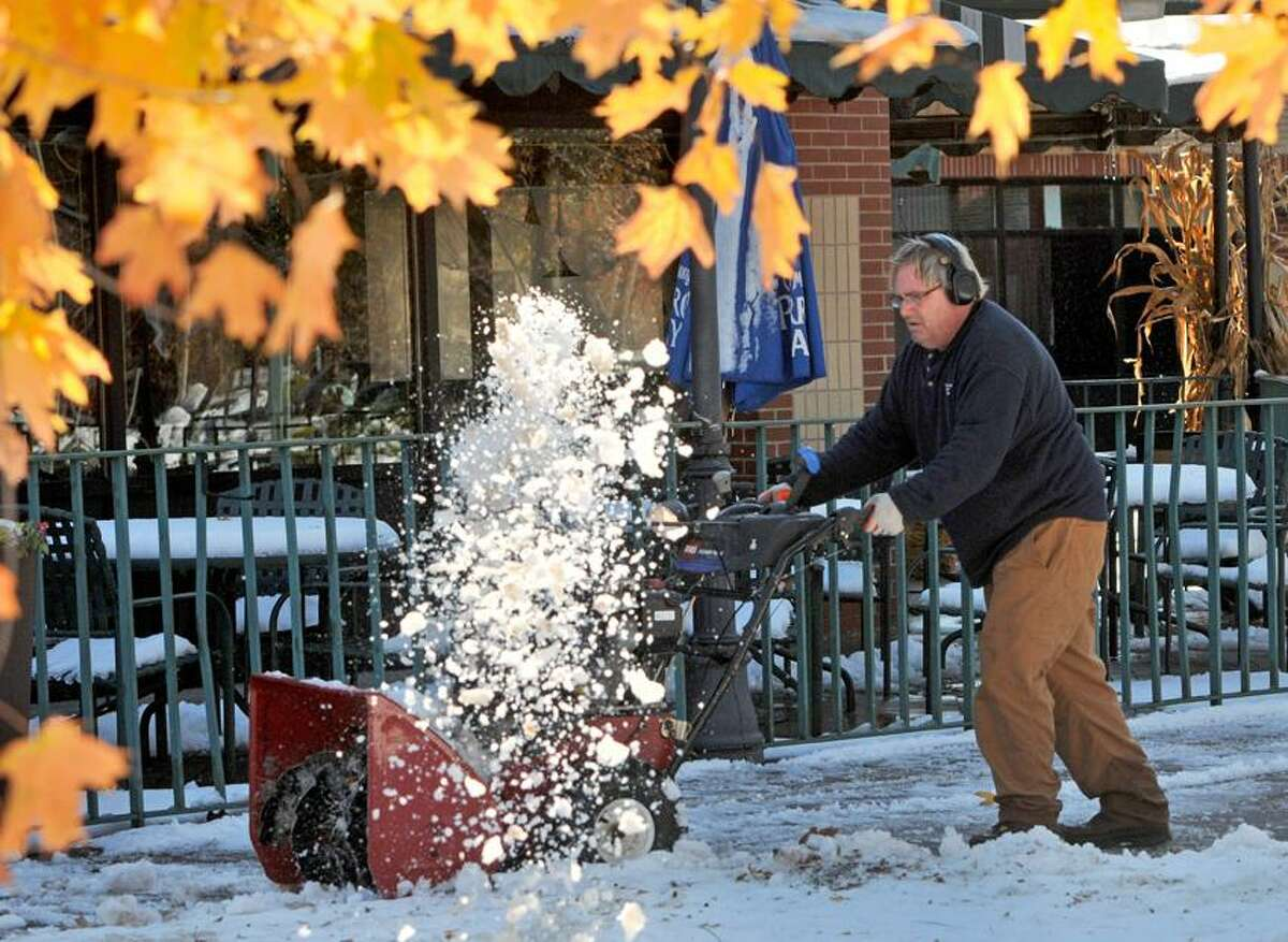 """Autumn's golden leaves serve as a counterpoint to the snow that is being removed by a snowblower operated Rob """"Froggy"""" Schiffer of Jake's Lawn & Garden in North Haven Sunday morning 10/30/11 as he clears the sidewalks around the office building and shops at Hamden Center near the corner of Whitney and Dixwell Avenues in Hamden. Looking forward to sleep, Froggy says that he started working after the snow started Saturday and through the night into Sunday. Connecticut was hit with a historic nor'easter that brought an October snowstorm Saturday. Photo by Peter Hvizdak / New Haven Register October 30, 2011 ph2397 # 2028 Connecticut"""