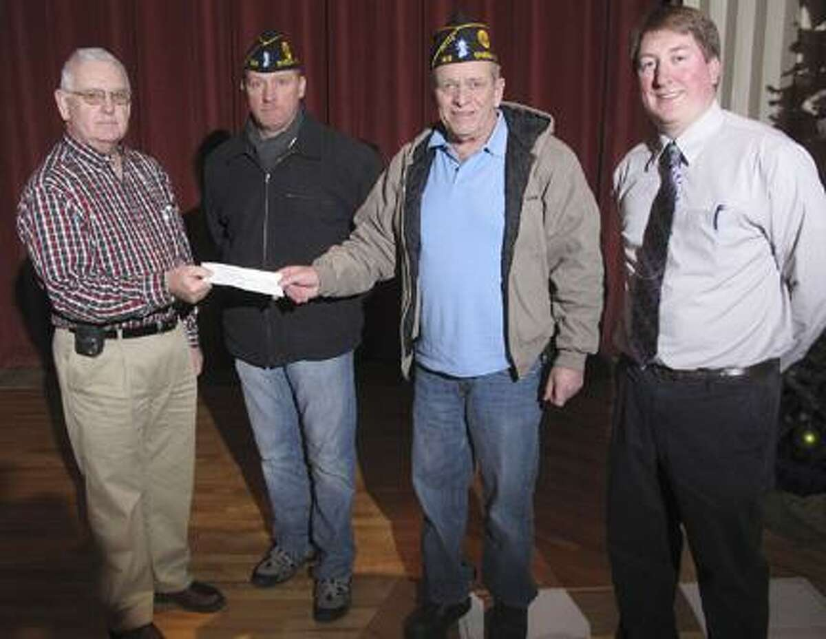 Dispatch Staff Photo by JOHN HAEGERAmerican Legion Post 169 Board of Directors President Tim Stevens and Legion Commander Joe Strong present a check for $3,000 to Ewrin Smith and Rotary President Scott Ingmire for the 5th annual veterans trip to Washington DC. The trip will be from April 18 through April 20, 2011.