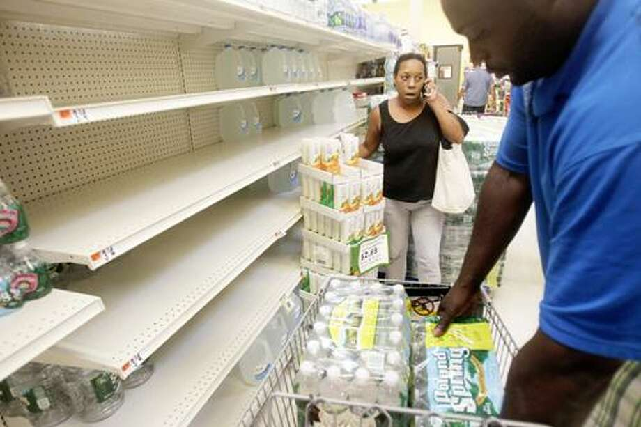 Shoppers stock up on water from rapidly emptying shelves at a grocery store in Far Rockaway in New York, Thursday, Aug. 25, 2011.  Mayor Michael Bloomberg on Thursday urged New York City residents living in low-lying areas to line up a place to stay on high ground ahead of a possible evacuation this weekend due to Hurricane Irene. (AP Photo/Seth Wenig) Photo: ASSOCIATED PRESS / AP2011