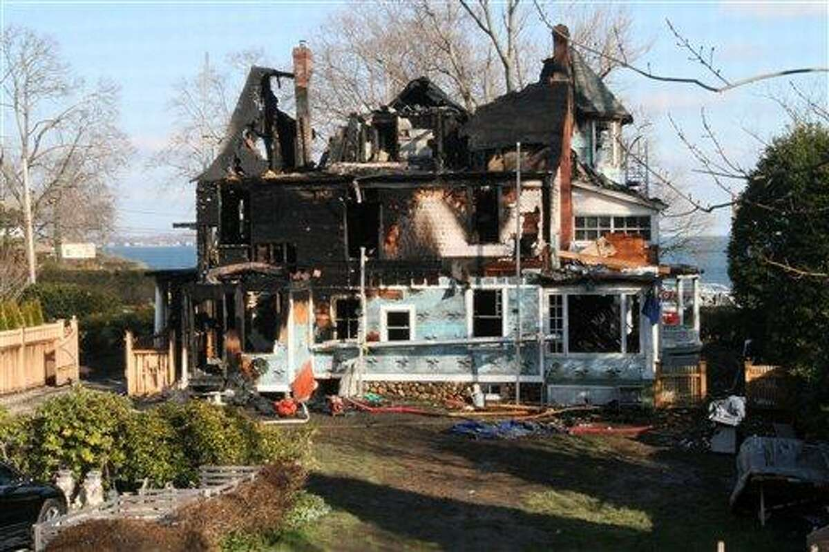 The back of a house where an early morning fire left five people dead is seen Sunday, Dec. 25, 2011, in Stamford, Conn. Officials said the fire, which was reported shortly before 5 a.m., killed two adults and three children. Two others escaped. Their names have not been released. (AP Photo/Tina Fineberg)