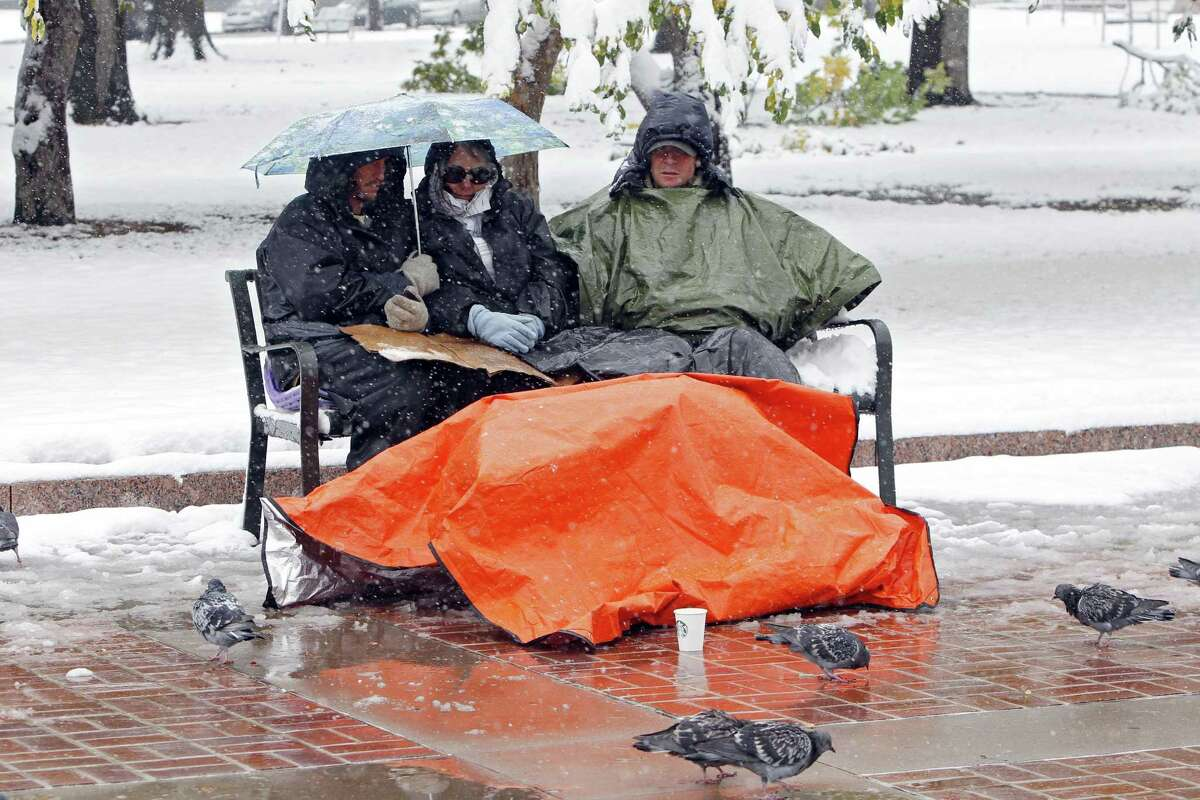 FILE - Wall Street protesters huddle under an umbrella and plastic to keep warm in City Park in Denver in this Wednesday file photo. A winter storm moved through the area bringing snow and freezing temperatures. (AP Photo/Ed Andrieski, File)