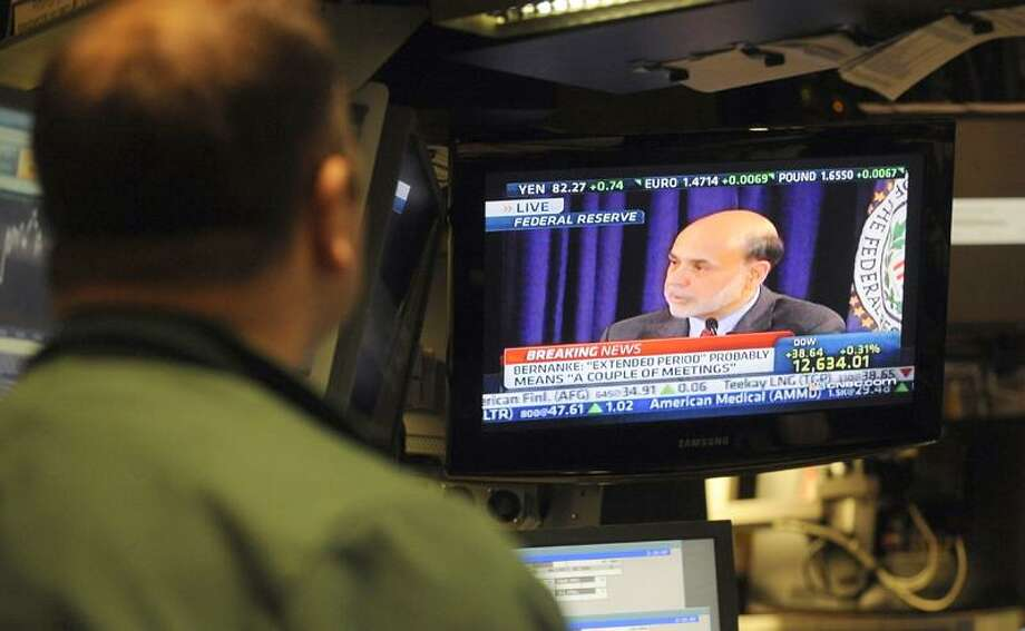 Federal Reserve Chairman Ben Bernanke is seen on a television on the floor of the New York Stock Exchange Wednesday. Bernanke said in the news conferencethat the Federal Open Market Committee would leave interest rates unchanged. Photo: AP / FR151332