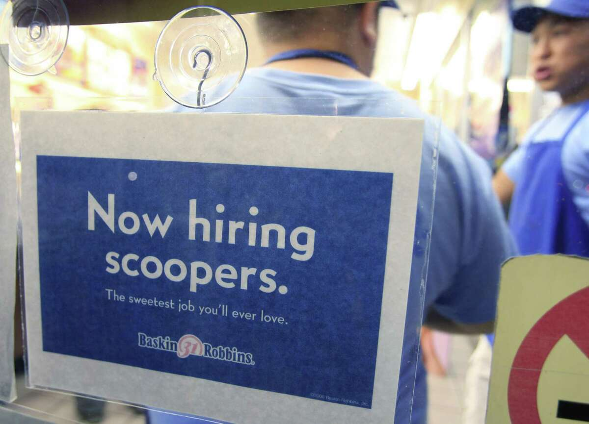 """A """"Now Hiring Scooper"""" sign is posted at Baskin Robbins 31 Flavors ice cream store as workers stand in background in Mountain View, Calif. on Wednesday. More people sought unemployment benefits last week, the second rise in three weeks, a sign of the slow and uneven jobs recovery.(AP Photo/Paul Sakuma)"""