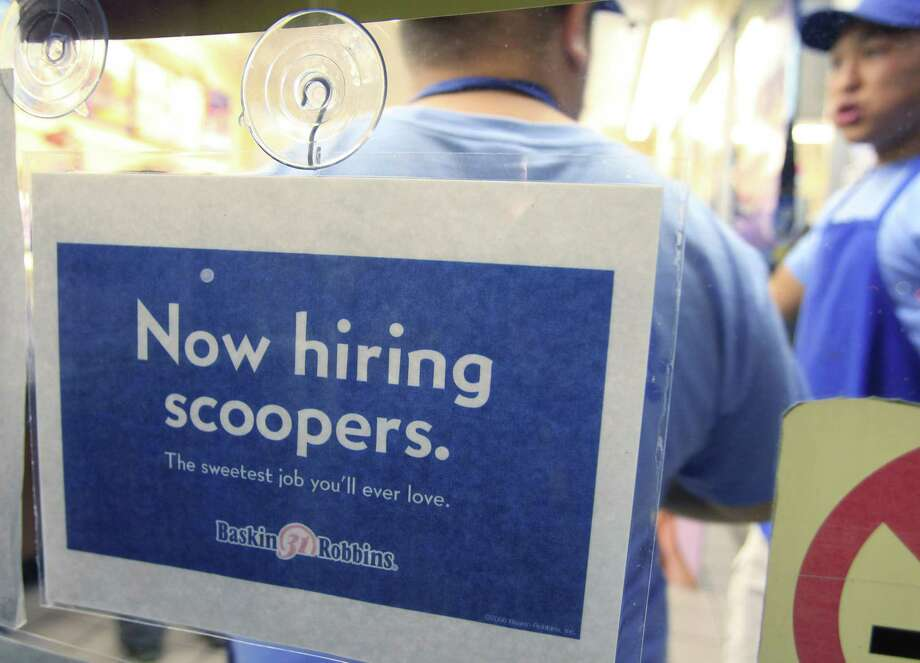 "A ""Now Hiring Scooper"" sign is posted at Baskin Robbins 31 Flavors ice cream store as workers stand in background in Mountain View, Calif. on Wednesday. More people sought unemployment benefits last week, the second rise in three weeks, a sign of the slow and uneven jobs recovery.(AP Photo/Paul Sakuma) Photo: AP / AP"
