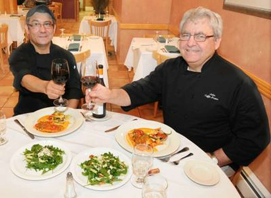 Photography by Peter Hvizdak            ph2190        #4043New Haven, Connecticut - October 25, 2010: Chef Santos Caceres, left, and owner/chef  John DiPaola with Tilapia Vesuvio, an entree and their Arugula Apple Walnut Salad at Caffe Bravo of New Haven.