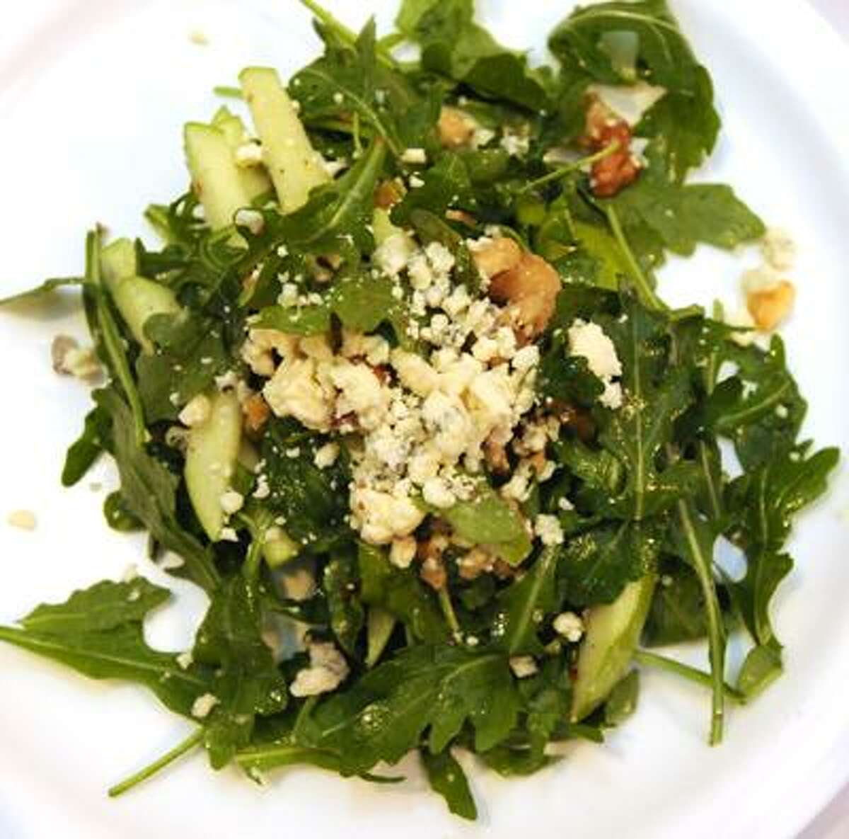 Photography by Peter Hvizdak ph2190 #4055New Haven, Connecticut - October 25, 2010: Arugula Apple Walnut Salad at Caffe Bravo of New Haven. Ingredients: Baby arugula, 1 tablespoon walnuts roasted 6-minutes at 400F depending on oven, 1 tablespoon gorgonzola cheese, 1/4 of a granny smith apple, 1 tablespoon of extra virgin olive oil, 1 tablespoon lemon juice, salt and pepper to taste.