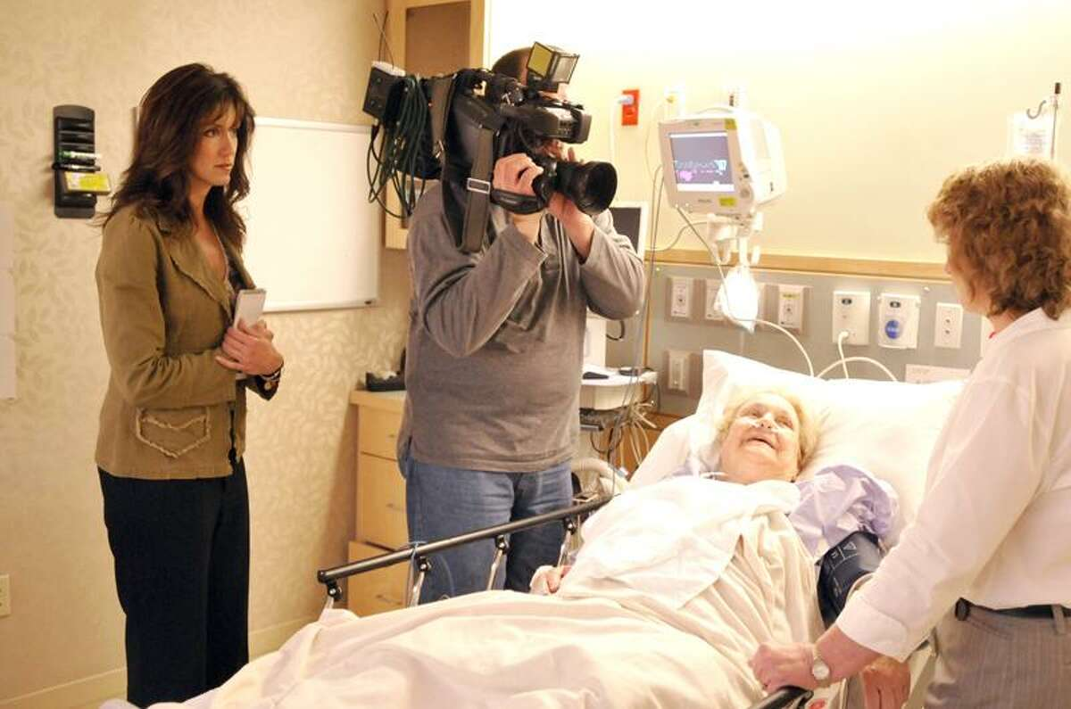 """Cusato and a News 8 videographer listen as registered nurse Paula Novak discusses """"healing touch"""" with Marie Bontempo of Norwich, who is not a dementia patient, at Backus Hospital in Norwich. Cusato's four-part series on Alzheimer's disease and dementia will air from 5-8 a.m. Tuesdays in May. (Jeff Evans/Backus Hospital)"""