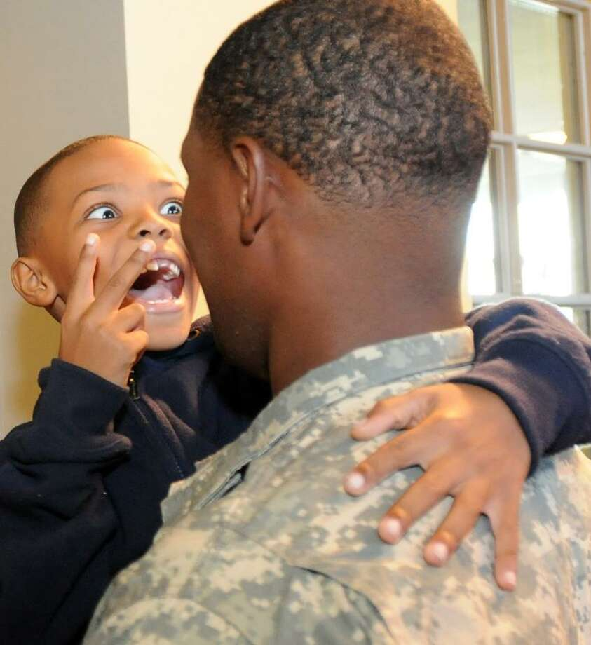 Alex, 7, a second-grader at the John C. Daniels School of International Communication in New Haven is excited to see his father, Nehemias, a serviceman in the Army who surprised him at the school Friday afternoon after just returning from an overseas deployment. The press was asked not to use their last name, the father's rank or unit name. Peter Hvizdak/Register / PETER HVIZDAK