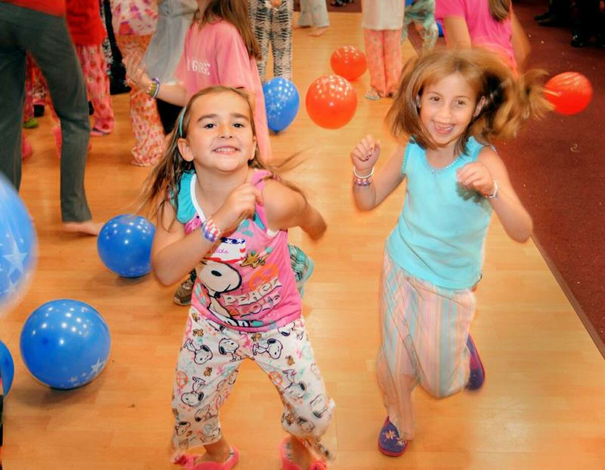 Alexa Suchy, 6, left, and Kimberly Evans, 6, both of Guilford, dance at the almost sleepover at the Knights of Columbus Hall. Melanie Stengel/Register