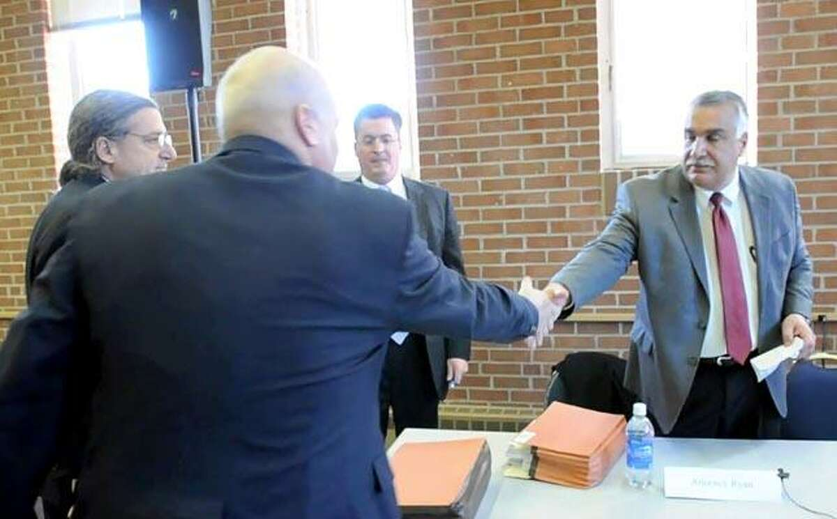 Deputy Chief Mike Doody, back to camera, and Police Chief Matthew Canelli reach across the table to shake hands after the chief's conciliatory statement Dec. 17. (Peter Hvizdak/Register photos)