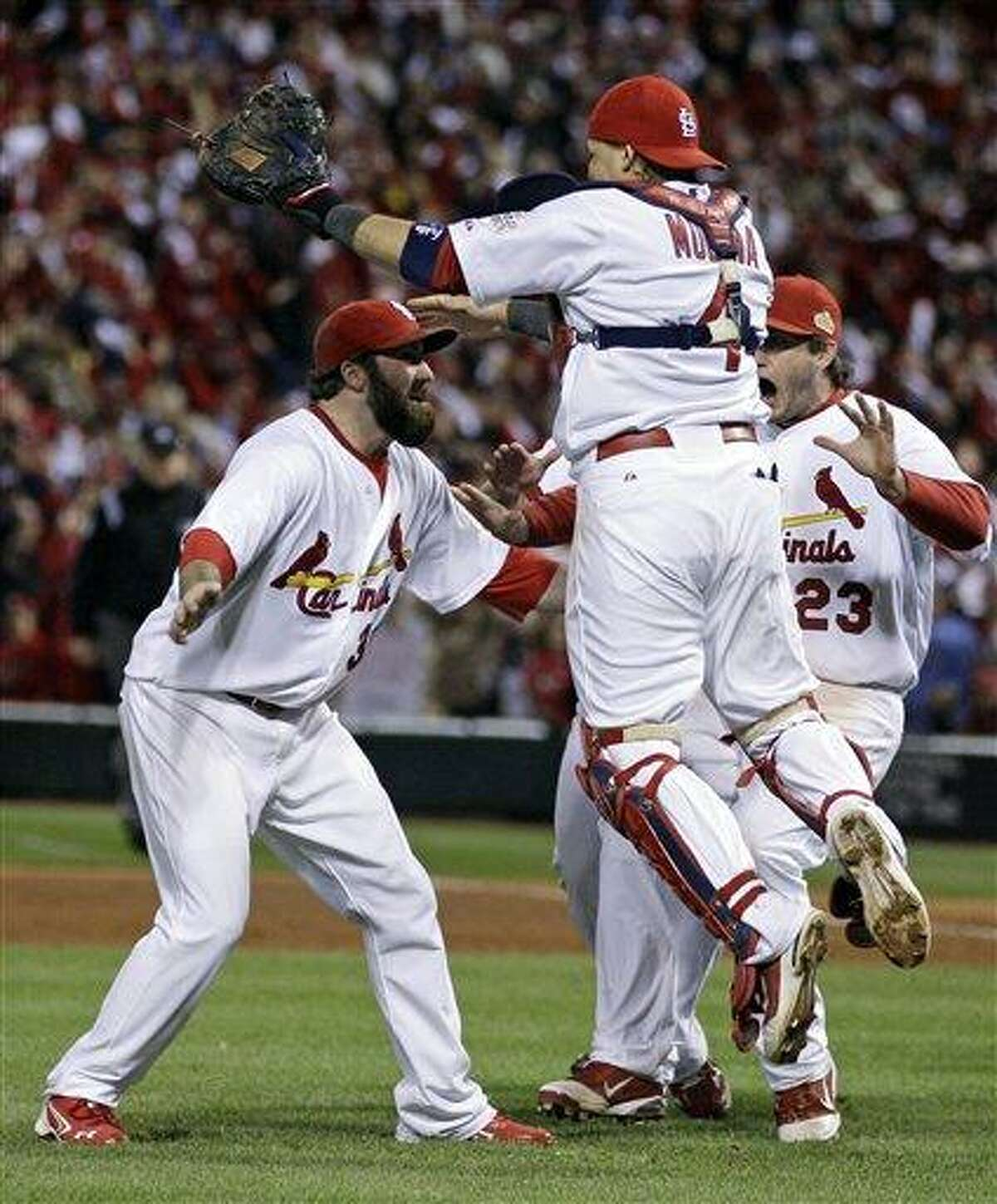 St. Louis Cardinals catcher Yadier Molina leaps in the arms of Jason Motte after Texas Rangers' David Murphy flies out to end Game 7 of baseball's World Series Friday, Oct. 28, 2011, in St. Louis. The Cardinals won 6-2 to win the series. (AP Photo/Matt Slocum)